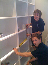 Two handymen installing shelves