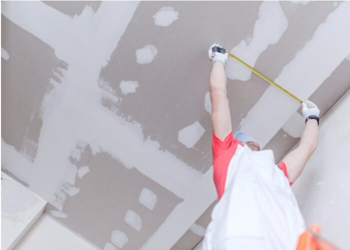 Handyman measuring while hanging drywall on ceiling.