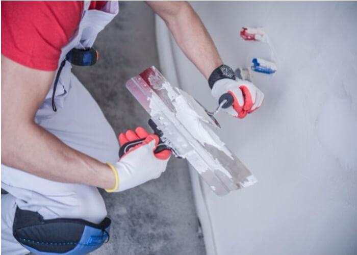 Handyman applying plaster on internal wall